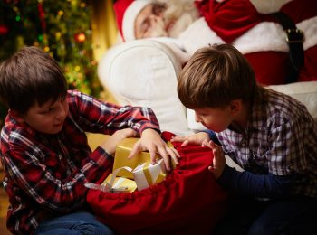 Curious boys choosing gifts from big red sack with Santa Claus sleeping on background